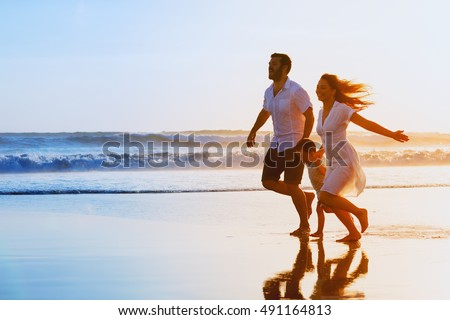 Happy family - father, mother, baby son hold hands and run together with fun along sunset sea surf on black sand beach. Travel, active lifestyle, parents with children on tropical summer vacations.