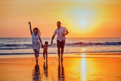 Happy family - father, mother, baby son hold hands and run with fun along sunset sea surf on black sand beach. Active parents and people outdoor activity on tropical summer vacations with children.