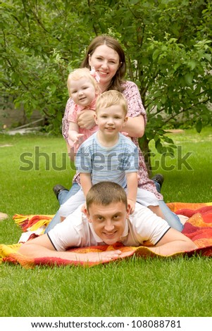 Happy family - father, mother, son, baby daughter on the grassy lawn. Family members sit on each other, forming a tower