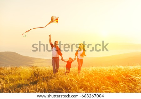 Happy family father of mother and child daughter launch a kite on nature at sunset