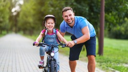 happy family father teaches child daughter to ride a bike in the Park in nature