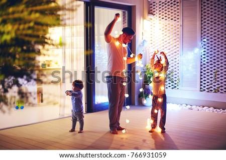 happy family, father with sons decorate open space patio area with christmas garlands
