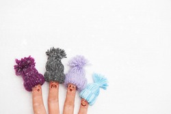 happy family fingers in warm knitted hats with bubonic rejoices first winter snow.