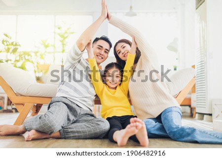 Happy family forming house roof with their hands at home