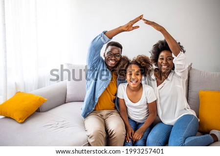 Happy family forming house roof with their hands at home. Insurance concept. Concept of housing and relocation. happy family mother father and kids with roof at home