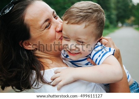 Happy family, friends forever concept. Smiling mother and little son playing together in a park. Mum holding shy baby. Sunny windy summer day. Outdoor shot #499611127