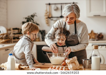 happy family grandmother and grandchildren cook in the kitchen, knead dough and bake cookies Сток-фото ©