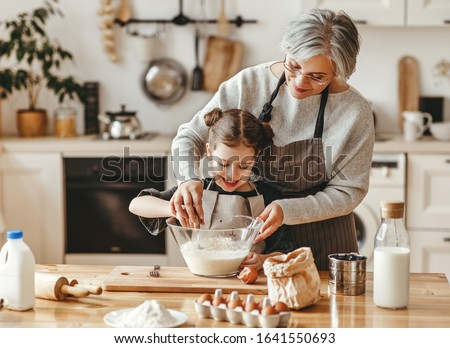 happy family grandmother and granddaughter child  cook in the kitchen, knead dough and bake cookies