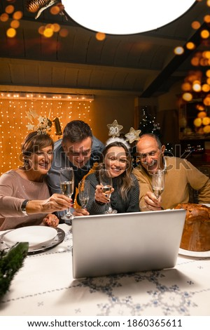 Happy family greeting their family and friends with a champagne glass, on New Year's eve using a skype video call. Relatives waving to a laptop. Social distancing during the coronavirus pandemic.