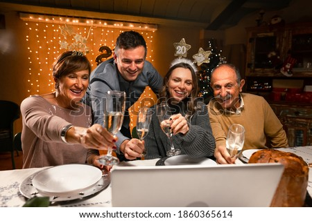 Happy family greeting their family and friends with a champagne glass, on New Year's eve using a skype video call. Relatives looking to a laptop. Social distancing during the coronavirus pandemic.