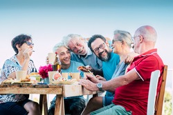 Happy family group celebrate together in friendship with fun and laugh - caucasian people enjoy food and drinks in celebration outdoor around the table - mixed generations from senior to young boy