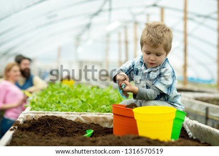 happy family. happy family workign with soil in garden. happy family in greenhouse. happy family in farm. new life #1316570519
