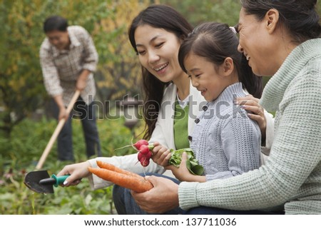 Happy family harvesting vegetables in garden