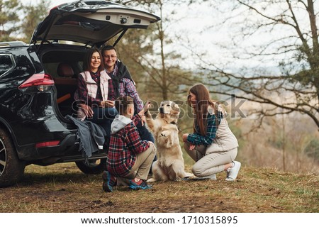 Happy family have fun with their dog near modern car outdoors in forest.