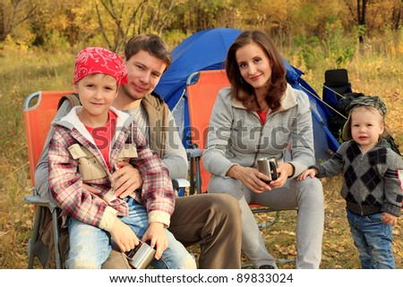 Happy family having a rest outdoor in tent.