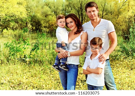 Happy family having a rest outdoor in the autumn park.