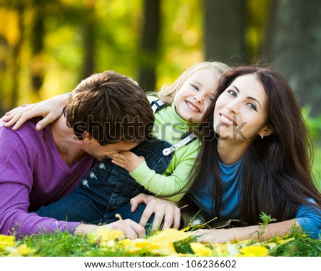 Happy family having fun against blurred autumn leaves background