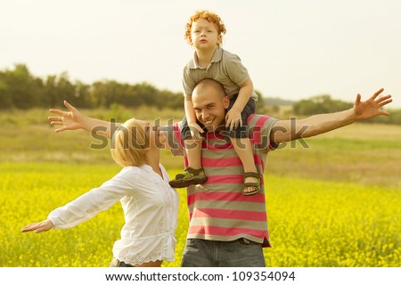 happy family having fun and doing plane figure in the field with yellow flowers. outdoor shot