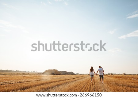 happy family having fun and walking on a field outdoors