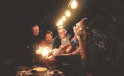 Happy family having fun at dinner night party outdoor - Group of people mixed ages celebrating together with fireworks sparklers outside - Holidays culture and parenthood lifestyle concept