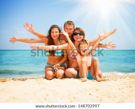 Happy Family Having Fun at the Beach. Joyful Family. Vacation and Travel concept. Summer Holidays. Parents with Children enjoying a holiday at the sea #148702997