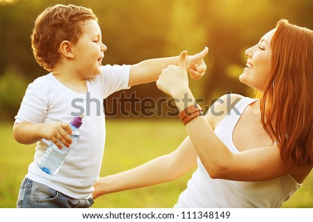 happy family having fun. baby boy with brown curly hair and  his mother with ginger hair showing thumb up each other. outdoor shot