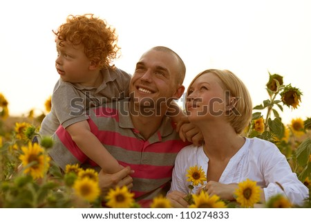 happy family having fun in the field of sunflowers. Father and mother watching something up in the sky. outdoor shot