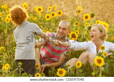 happy family having fun in the field of sunflowers. Son pulling his parents. outdoor shot