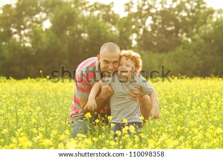 happy family having fun in the field with yellow flowers. Father and his son. outdoor shot