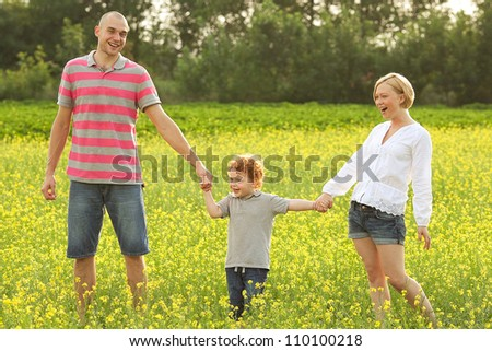 happy family having fun in the field with yellow flowers. outdoor shot