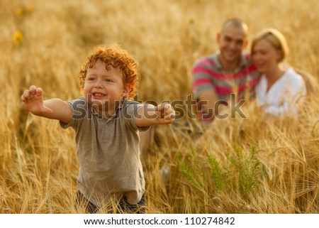 happy family having fun in the wheat field. Father and mother behind their son. Son's hands up. outdoor shot