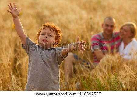 happy family having fun in the wheat field. Father and mother behind their son. Son\'s hands up. outdoor shot