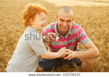 happy family having fun in the wheat field. Father doing soap bubbles to his son.