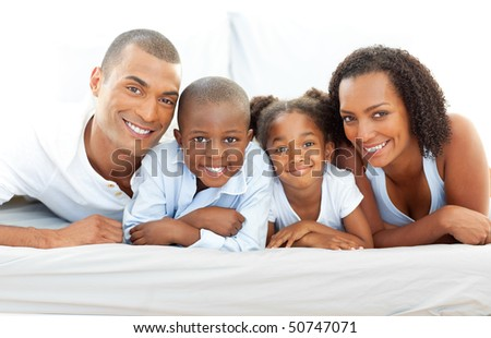 Happy family having fun lying down on bed at home