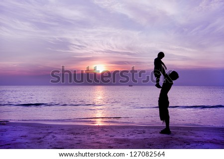 Happy family having fun on the beach,Father and son play on the Beach in sunrise silhouette shot