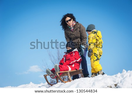 Happy family having fun on the snow with sled.