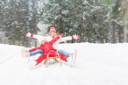 Happy family having fun outdoor. Mother and child playing in winter time. Active healthy lifestyle concept