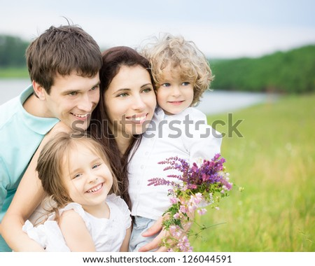 Happy family having fun outdoors in spring field against blurred grass and sky background