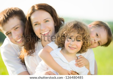 Happy family having fun outdoors in spring field against natural green background