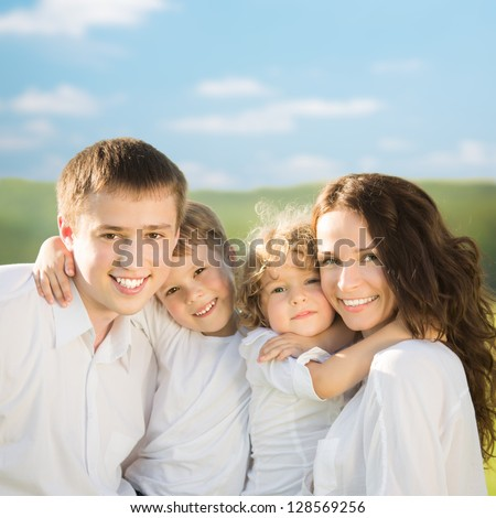 Happy family having fun outdoors in spring green field against blue sky background