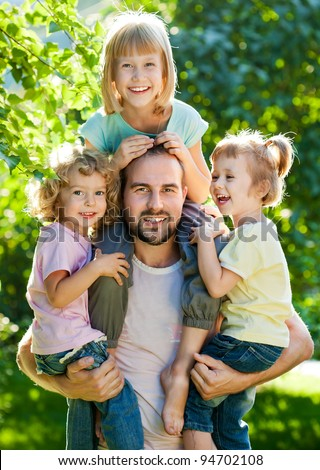 Happy family having fun outdoors in spring park against natural green background