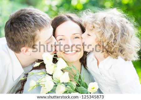 Happy family having fun outdoors in spring park against nature green background. Mother`s day concept