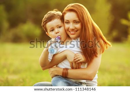happy family having fun. son drinking water from the plastic bottle, mother holding him. outdoor shot.