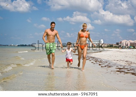 Happy family having good time on a beach. - stock photo