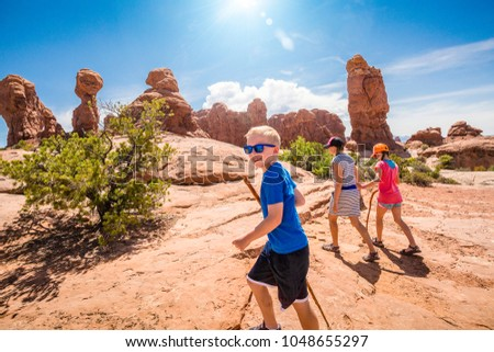 happy family hiking together in the beautiful rock formations of Arches National Park. Walking along a scenic trail with large rock unique formations in the background