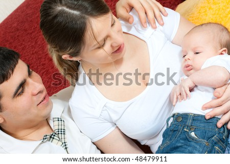 happy family home: father, mother and baby sitting on the floor in living room