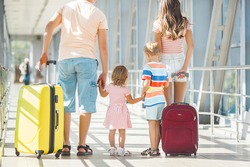 Happy family in airport departures. People in terminal preparing for the vacation
