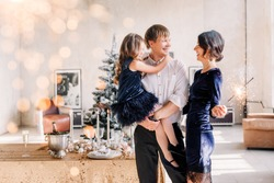 Happy family in blue - woman, man and little girl, with a sparkler in hand, near the New Year's table for Christmas at home. The girl at the father on hands. New year 2020. Parents look at each other