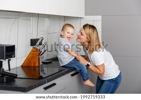 Happy family in casual denim in a kitchen room. Little boy with his mother at home. Good morning  parent and infant son in jeans wear. Family weekdays traditions. Relationship with love
