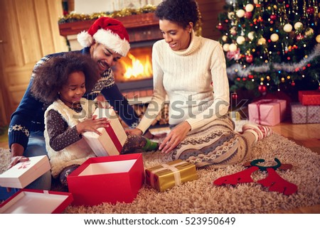 Happy family in Christmas morning opening present in home front of Christmas tree
